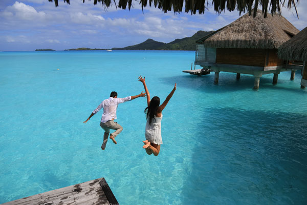 Happiness jump of young couple into the water near bungalows at Bora Bora, French Polynesia