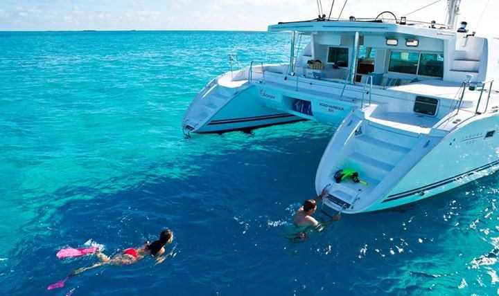 Couple Swimming Up To Aft on 50' catamaran DORIS