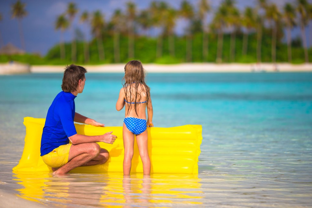 Little girl and young father with yellow float Caribbean Island beach vacation