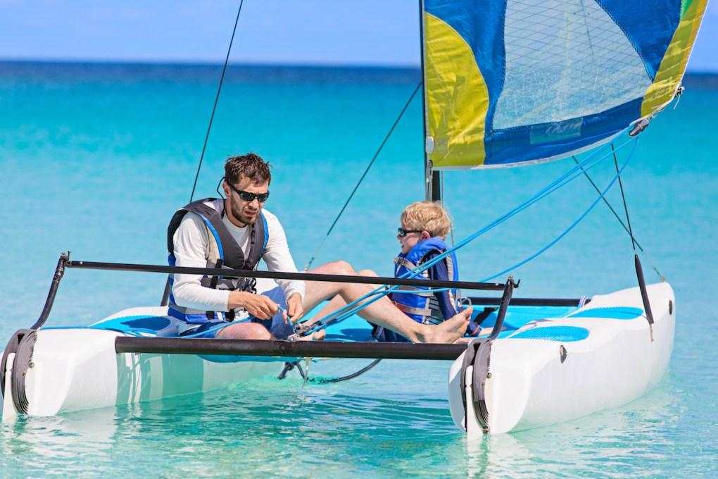 father and son, enjoying sailing together at hobie cat catamaran