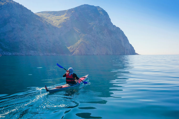 Man kayaking in the calm blue waters of the sea.