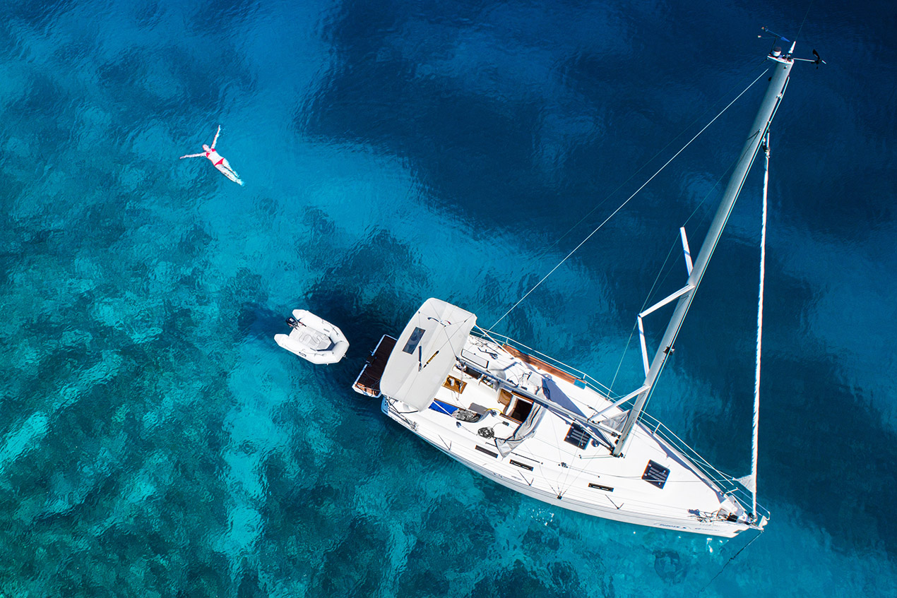 aerial view of sailing yacht, swimming woman and clear water in a Caribbean paradise