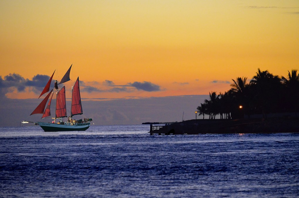 Red-sailed boat sailing around Key West, Florida at sunset