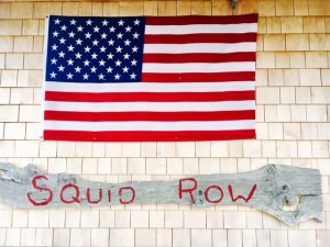 Squid Row sign and American flag on shingled building Martha's Vineyard Nantucket getaways by land and sea