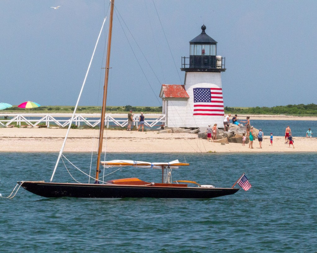 Sailboat moored off lighthouse beach with American flag Nantucket