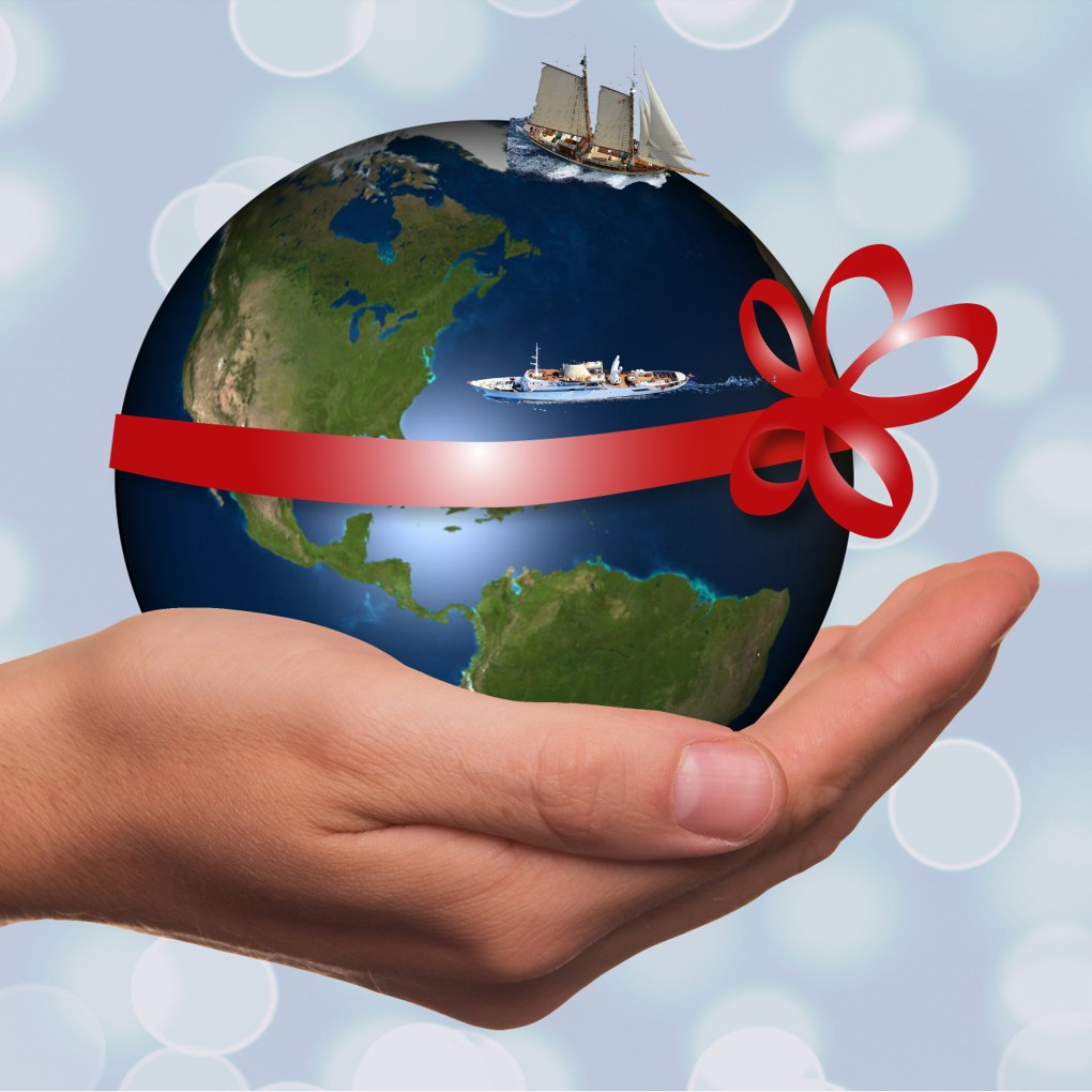 Globe in hand with sail boat, motor yacht and wrapped in a red ribbon