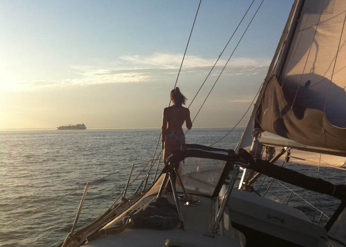 Woman looking out to sea from the bow of the sailing yacht INDEPENDENCE