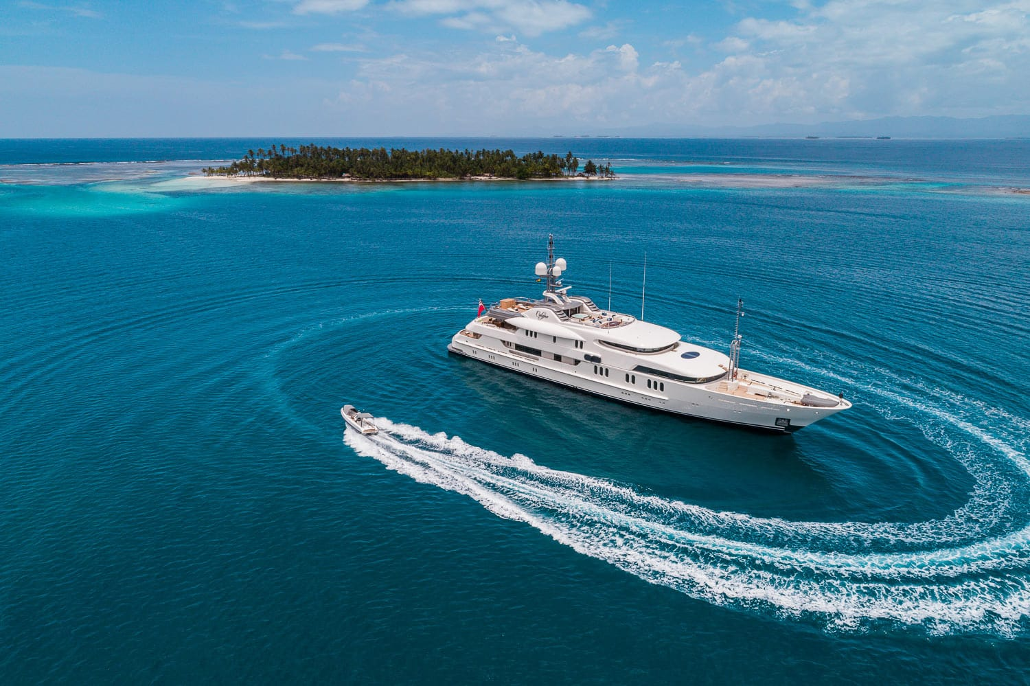 Aerial view of 202ft Amel motor yacht CALYPSO w tender circling boat