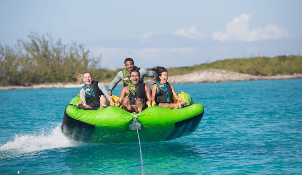 Raft full of laughing yacht charter couples pulled by motor yacht LADY JOY