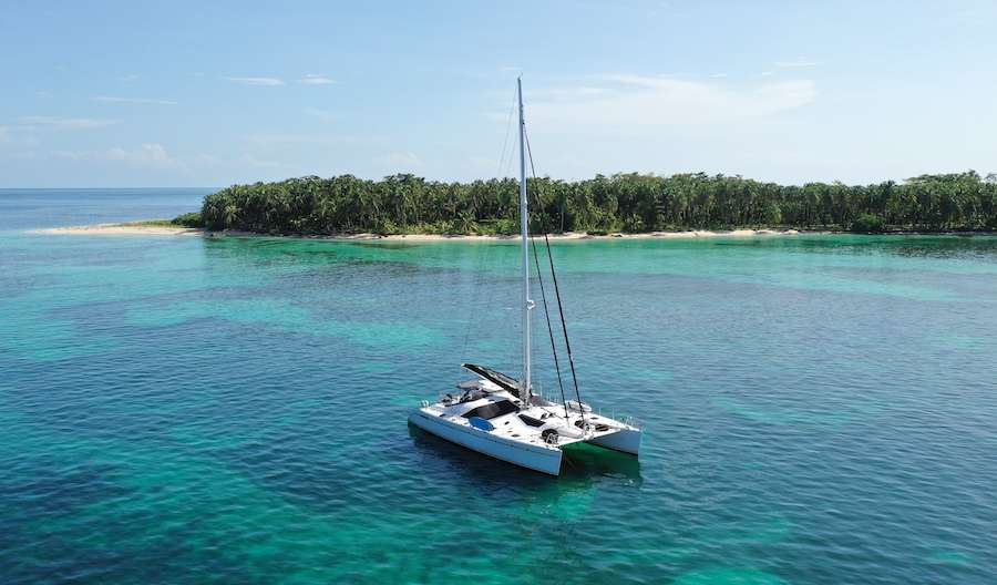Sailing catamaran LOLALITA anchored off tiny island in the Caribbean