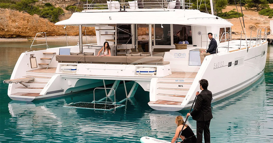 Stern shot of 60ft Lagoon sailing catamaran MOYA at anchor with guests standup paddleboarding to steps