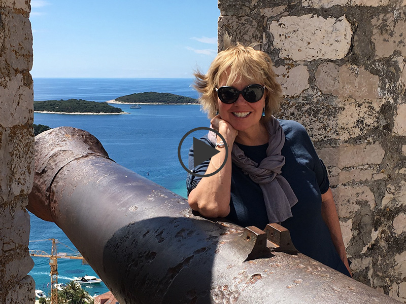 Carol Kent leaning on a cannon at a fortress in Croatia overlooking the sea