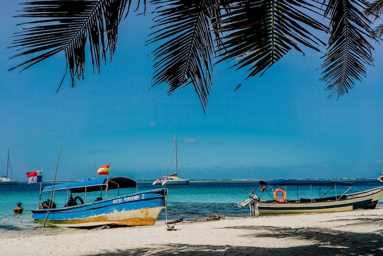 Boats on and off one of Panama's white sandy beaches