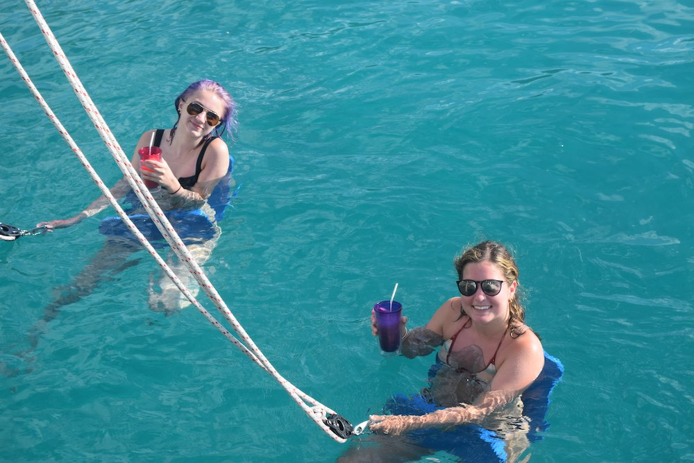 Mother and daughter float in submerged chairs with drinks off S/Y catamaran STOP WORK ORDER in St. Croix