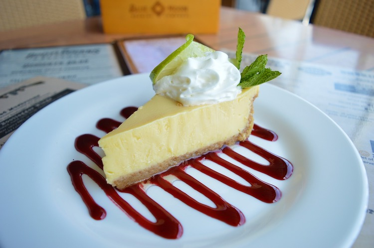 Slice of Key lime pie on a plate with red berry sauce, whipped cream and menus