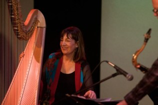 Photo of Carol Robbins with harp on stage at Alvas Showroom, San Pedro CA November 23, 2013