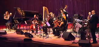 photo of Moira Smiley singing onstage with Carol Robbins on harp, Billy Childs and the other artists in the orchestra