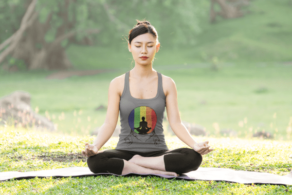 A woman enjoying yoga meditating in the woods wearing a unique design - bathing in the rainbow.