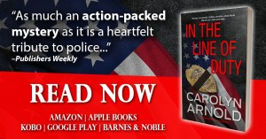 In the Line of Duty by Carolyn Arnold Read Now, badge with morning band covering the middle of the badge resting on a rippled US flag.
