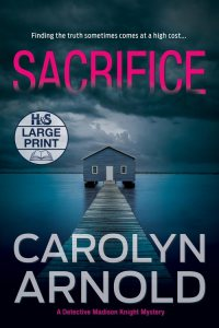 Sacrifice Large Print Edition by Carolyn Arnold, a boathouse at the end of a dock sitting in a frozen river under a cloudy sky