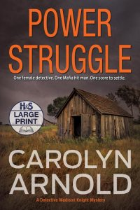 Power Struggle Large Print Edition by Carolyn Arnold, rundown barns in a field with a stormy sky.