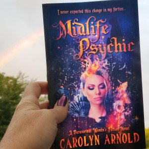 Midlife Psychic by Carolyn Arnold in her hand with a rainbow in the sky