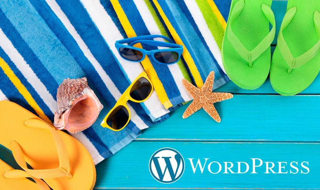 Beach towel, flip flops,starfish, sunglasses and the WordPress logo on a turquoise wooden deck