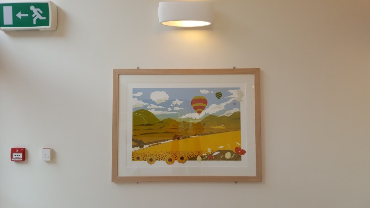 Image of the 'Serenity' linocut by Carolyn Murphy on the wall at the Macmillan Centre