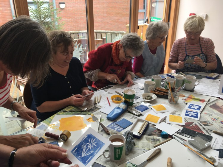 Image of members of the Macmillan Craft & Chat group cutting lino