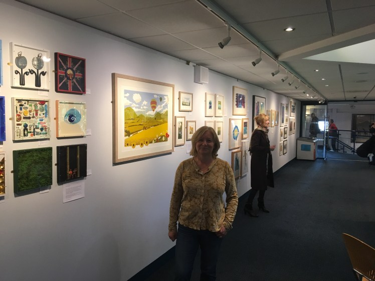 Image of artist and printmaker Carolyn Murphy with her work at the exhibition