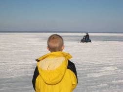 Zachary watching Kevin M. and Luke on the snowmobile