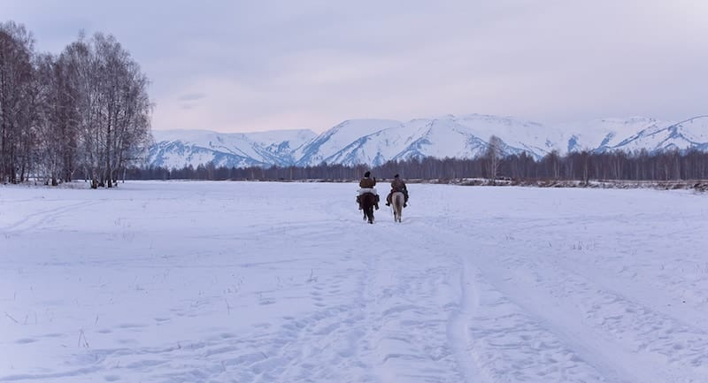 Two shepherd or cowboy riding a horse over the snowy mountains
