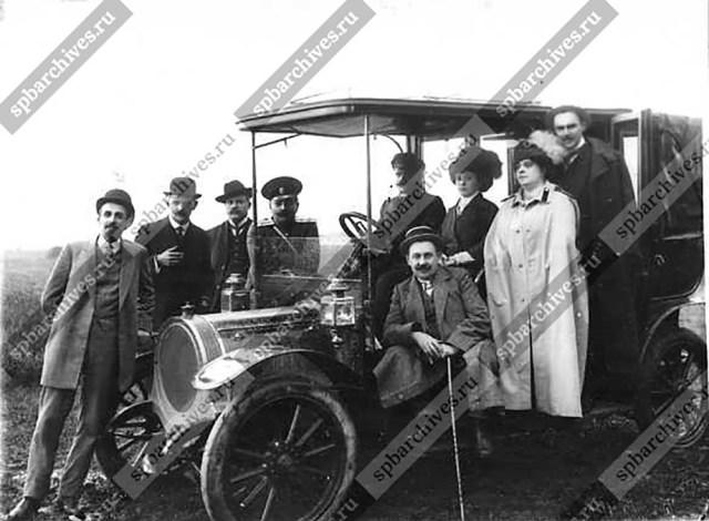 1910 . Группа участников Первой авиационной недели на Коломяжском ипподроме у автомобиля. Санкт-Петербург .
