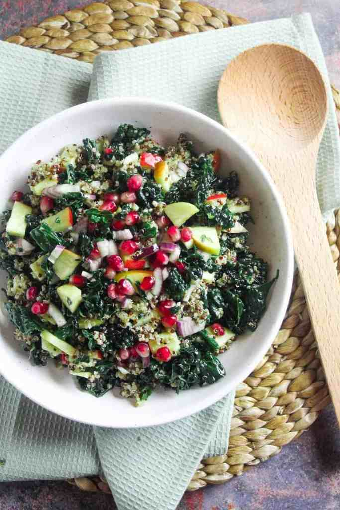 Bowl of kale and pomegranate salad with a lemon thyme vinaigrette. Shown in a white bowl on a woven mat with a wooden serving spoon.