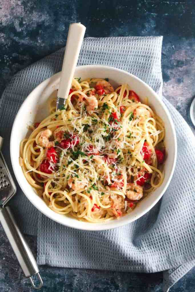 Linguine pasta tossed with king prawns, tomato and chilli and topped with grated parmesan cheese. In a white bowl placed on a blue towel.