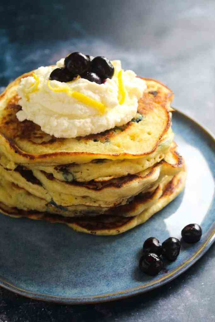 A stack of thick and fluffy pancakes topped with a dollop of mascarpone cream. Garnish with blueberries and lemon zest.