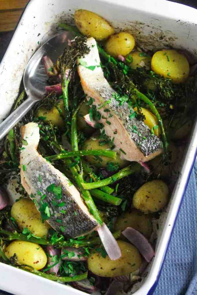 Roasting tin containing two salmon fillets on a bed of roast new potatoes, tenderstem broccoli and wedges of red onion.