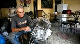 "Sergio Morales working on the engine of an old Harley-Davidson motorcycle in his dining room, where he does most of his restoration work. ""These engines are practically immortal,"" he says. Credit Jose Goitia for The New York Times"
