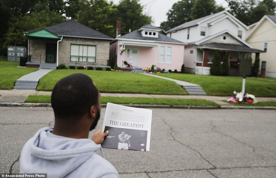 Dearejon White, of Louisville, Ky., holds up a newspaper as he tries to take a photo of it with Muhammad Ali's childhood home, center rear, in the background, Sunday, June 5, 2016, in Louisville. Ali, the magnificent heavyweight champion whose fast fists and irrepressible personality transcended sports and captivated the world, died Friday at the age of 74. (AP Photo/David Goldman)