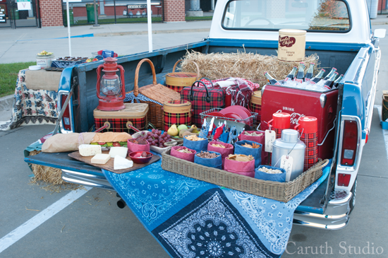 tailgate of a vintage truck loaded with food and party goodness