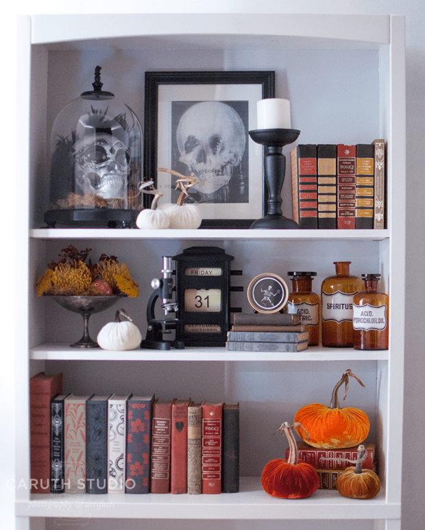 Halloween bookshelf with 3 shelves decorated with books and Halloween themed decorations