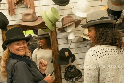 Mom and Daughter team trying on top hats