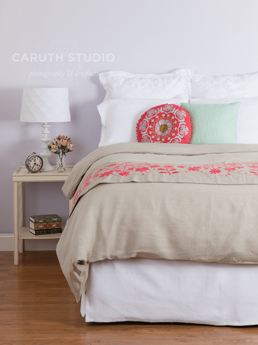 bedside with coordinating linen bedspread, pink and kaki bed runner, circular pink pillow, mint square pillow and white sheets with coordinating bedside table