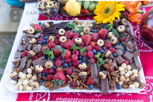fall themed chili party dessert platter with berries, chocolate and acorn shaped chocolate kisses
