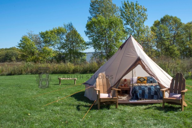 tipi tent overlooking lake in grassy field