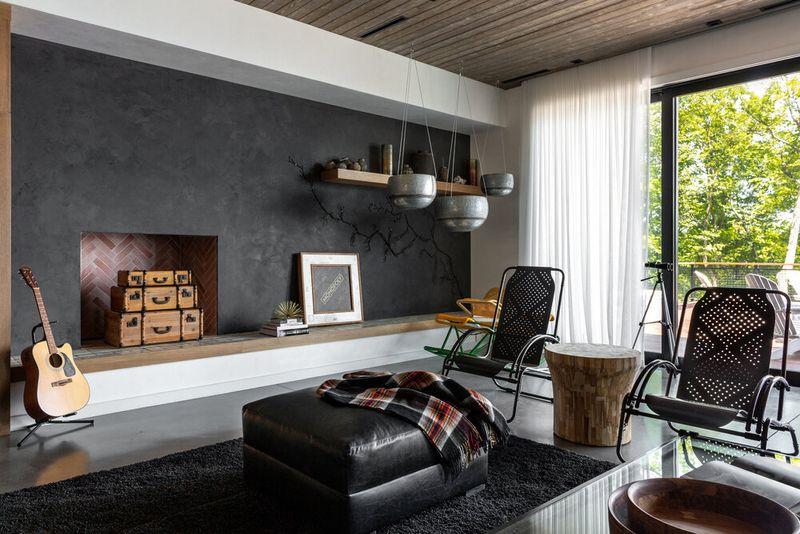 """<span style=""""font-weight: 400"""">As cores escuras podem ser difíceis de usar, mas não é o caso com esse estilo. Se seus tetos não forem altos, tons mais escuros - como preto, carvão ou marinho - certamente complementarão alguns dos materiais na casa.</span>"""