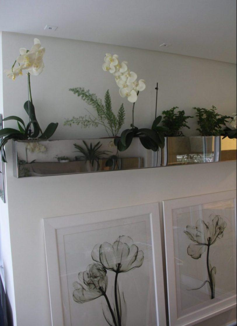 Quadros apiados sobre prateleira em obra do arquiteto Adriano Gronard. Vaso em aço inox polido com nichos internos para possibilitar a alternância de plantas conforme a época