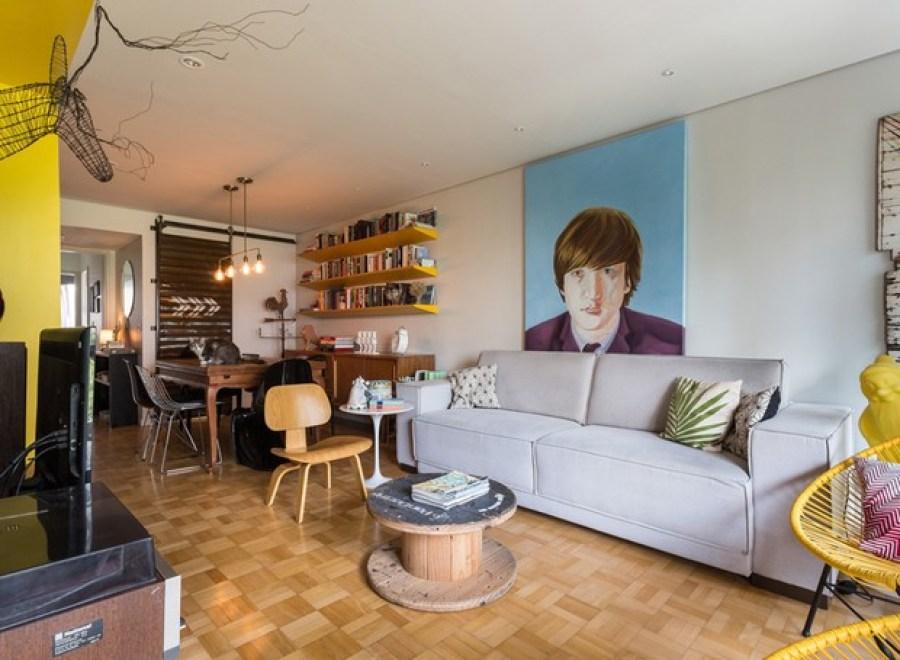 Pisos de madeira, madeira natural, parquet. Sala com piso parquet de madeira, sofá cinza, mesa de antiquário, prateleiras amarelas, quadro de John Lennon. Casa ao Cubo.