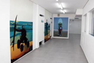 corredor da escola com figuras e fotos de pessoas com deficiência impressas na parede #pracegover