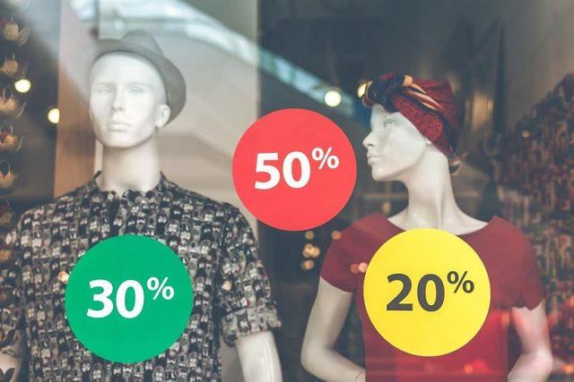 """Vitrine de uma loja de roupas. Dois manequins aparecem da cintura para cima. O da esquerda é um manequim masculino, com chapéu cinza e camiseta estampada cinza e preta. À direita um feminino, com lenço vermelho amarrado na cabeça e uma blusa vermelha. Na frente deles, grudados na vitrine, há três adesivos redondos de cores verde, vermelho e amarelo indicando os valores """"30%"""", """"50%"""" e """"20%""""."""